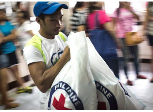 Volunteers and staff working with food items at Philippine Red Cross HQ.