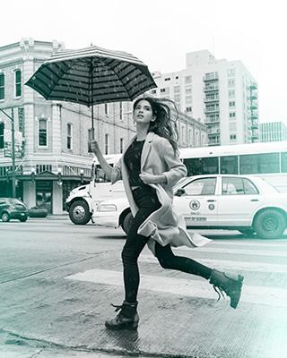 A girl running in boots carrying an umbrella.