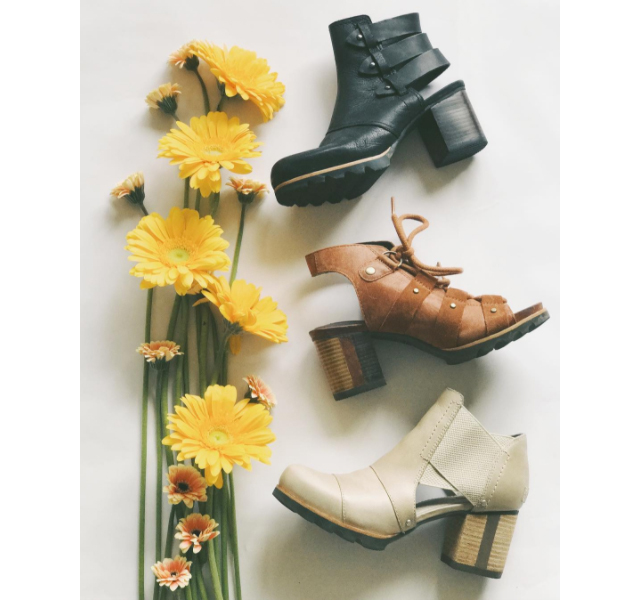 Three stacked heeled sandals with yellow flowers.