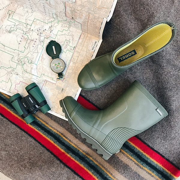 An image of green rain boots and binoculars.