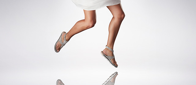 A girl jumping in strappy sandals.