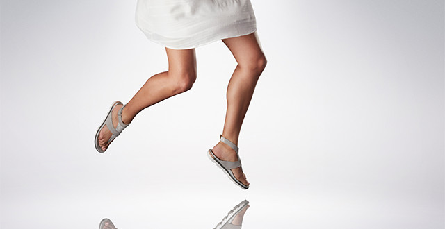 A woman dancing in grey sandals.