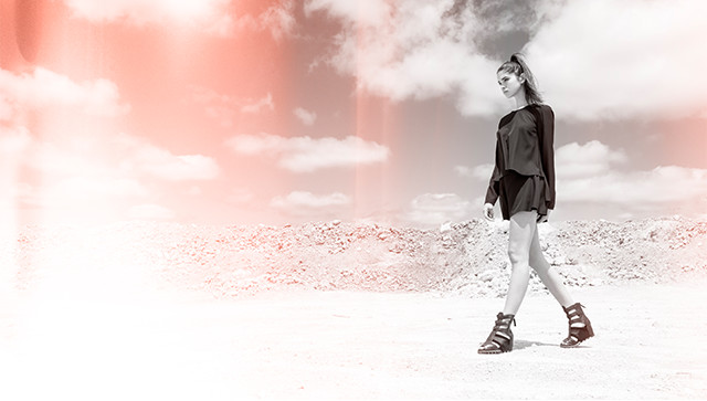 A young woman wearing gladiator sandals walks through the desert.