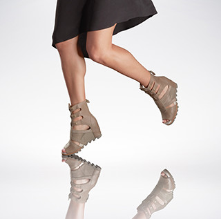 A woman wearing gladiator sandals and a skirt.
