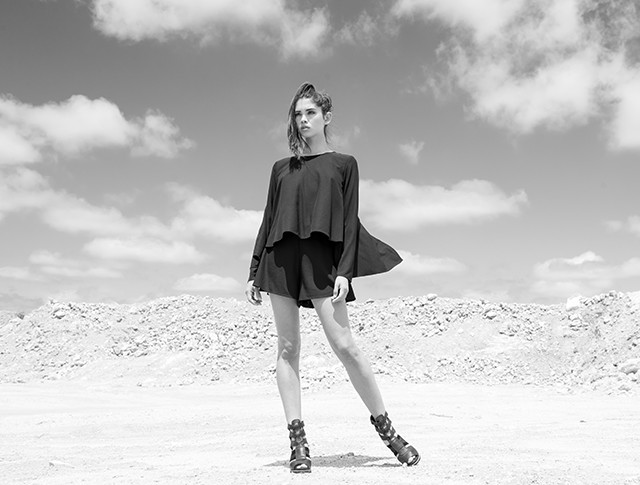 A young woman in the desert in shorts and gladiator sandals