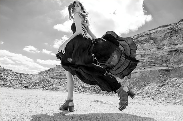 A young woman running in heels in the desert.