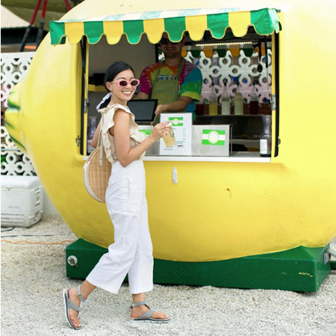 A woman at a lemonade stand wearing Torpeda Ankle Strap sandals.