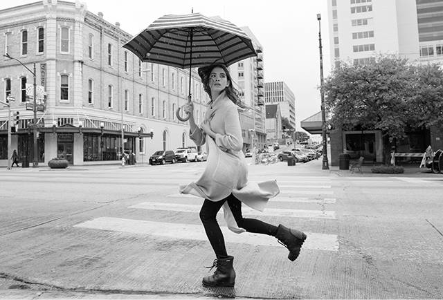 A woman in rain boots with an umbrella running  down the street.