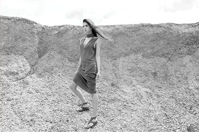 A young woman standing below a desert ridge wearing a dress and sandals.