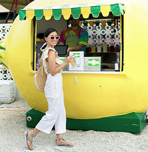 A young woman at a lemonade stand wearing Torpeda Ankle Strap sandals.