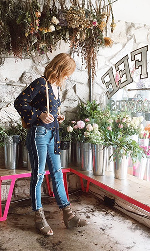 A woman looks at flowers in a florist shop while wearing Joanie Gladiator wedge sandals.