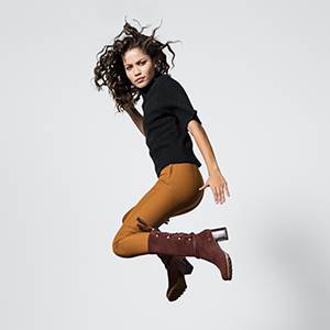 A young woman jumping in knee-hi boots.