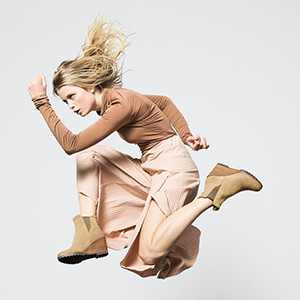 A young woman jumping in wedge boots.