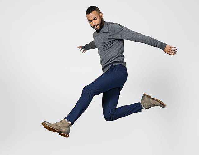 A young man jumping in boots.