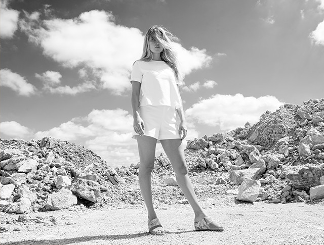 A young woman in sandals and shorts in the desert.