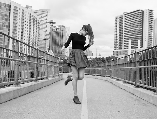 A young woman wearing a top, skirt, and ankle boots poses on a bridge.