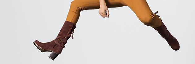 A woman jumping in mid-cut boots.