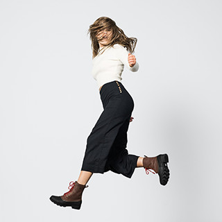 A young woman jumping in boots.