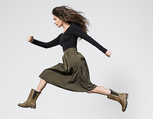 A young woman running in boots.