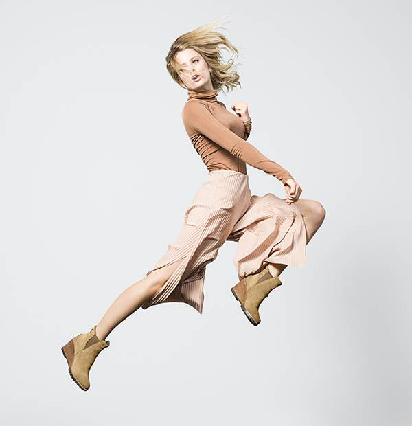 A young woman jumping in wedge ankle boots.