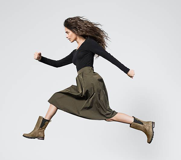 A young woman jumping in mid-calf boots.