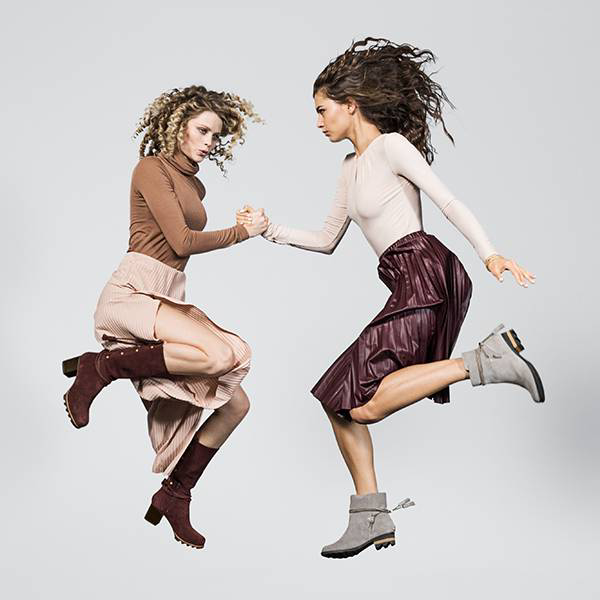 Two young women jumping, while holding hands, in two different boots.