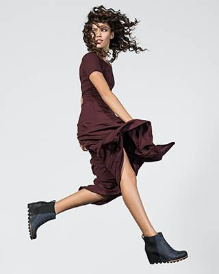 A woman jumping in ankle boots.