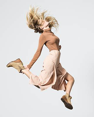 A woman jumping in wedge booties.