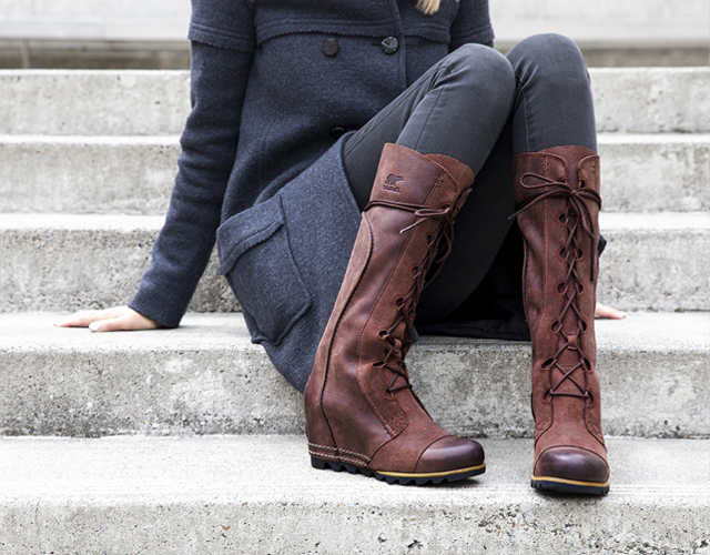 Close-up of a woman wearing the redwood Cate The Great Wedge Boot.