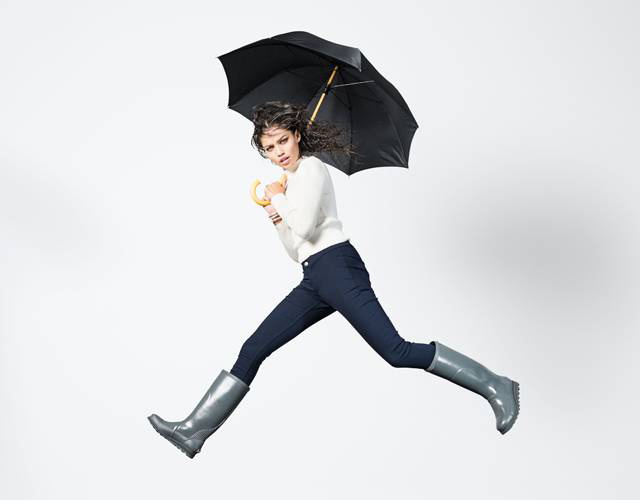A young woman jumping in rain boots.