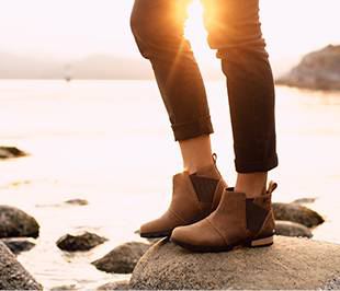 A young woman standing on a rocky shoreline wearing light brown Emelie Chelsea boots.