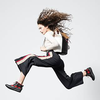 A young woman jumping in ankle boots and a backpack.