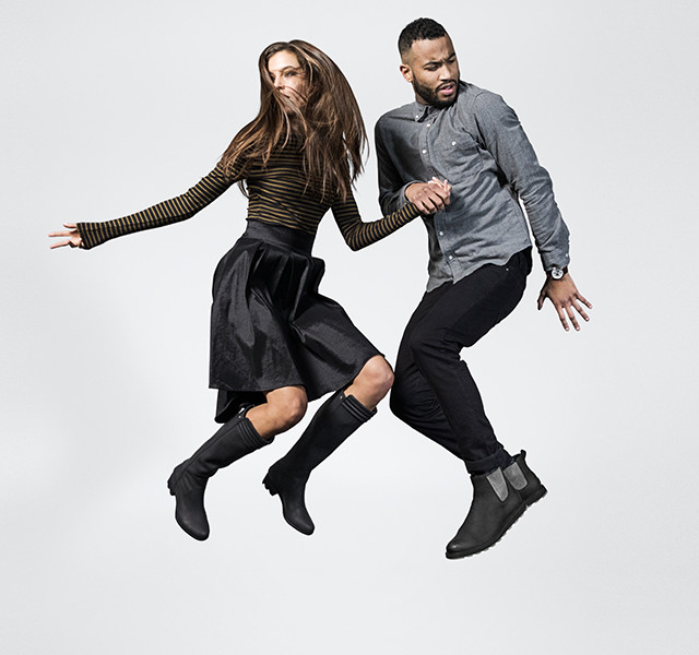 A young woman and man jumping in boots.