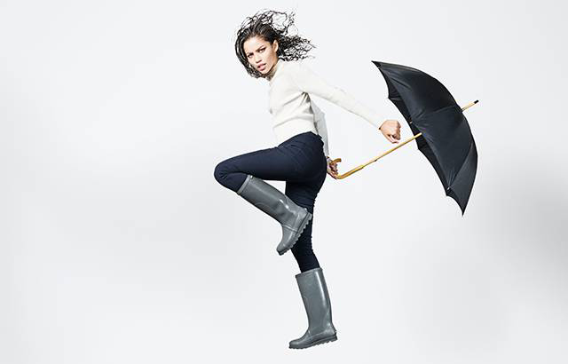 A woman jumping in rain boots with an umbrella.