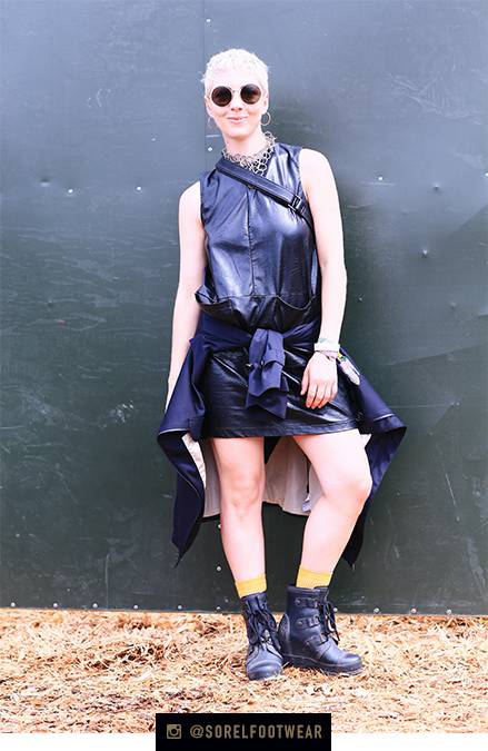 A young woman in rain boots and a dress.