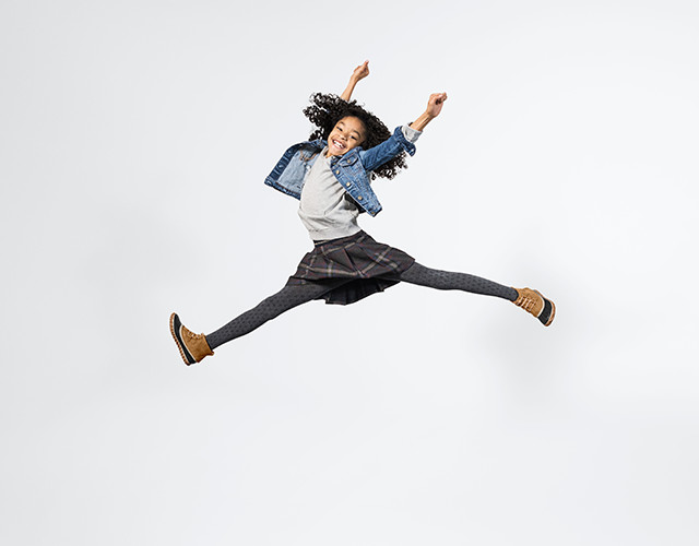 A young girl jumping in boots.