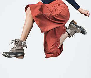 Partial shot of woman jumping in boots.