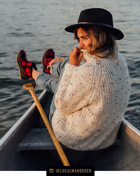 A young woman sits in a canoe with her feet propped up wearing Whitney Camp boots in a buffalo check pattern.