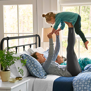Mother and daughters playing in a bedroom.