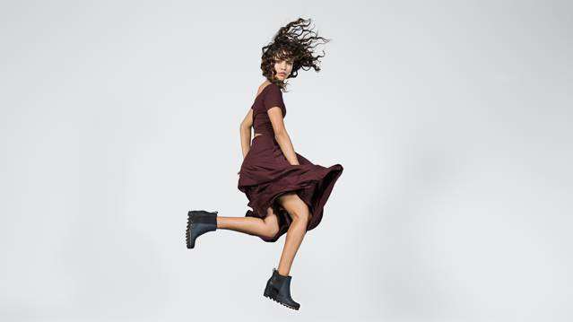 A young woman jumping in blue boots.