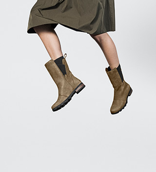 A woman jumping in boots.