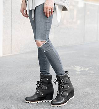 A woman standing in ankle wedge boots.
