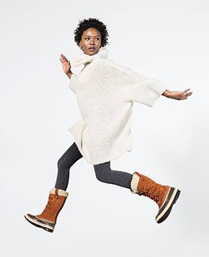 A young woman jumping in tall boots.