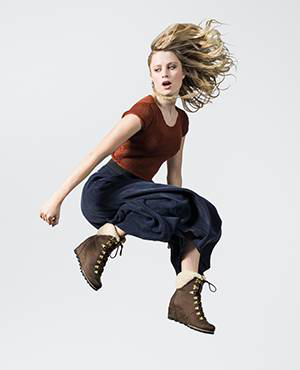 A young woman jumping in ankle boots.