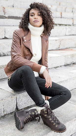 A woman sitting in wedge ankle boots.