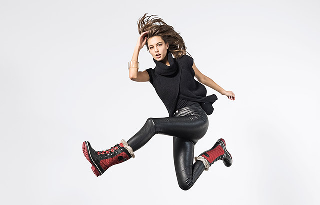 A young woman jumping in red boots.