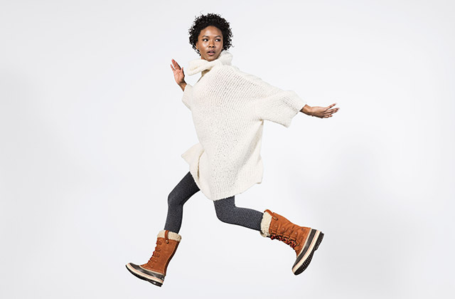 A woman jumping in winter boots.