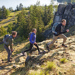 Group of people hiking up a mountain trail.