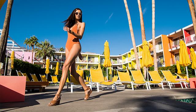 Woman walking by a pool in Joanie Sandals.
