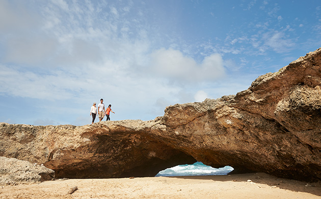 Image of people on a natural rock bridge in Aruba - Click here to book now